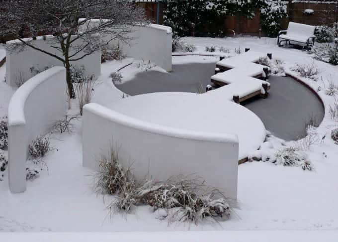 A blanket of snow highlights the stark beauty of the walls as they spin out from the pond