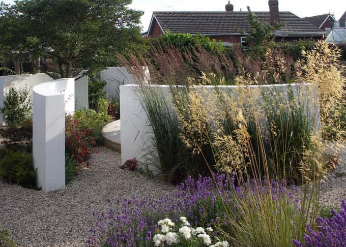 The screen walls form a foil for soft airy grasses and flowers