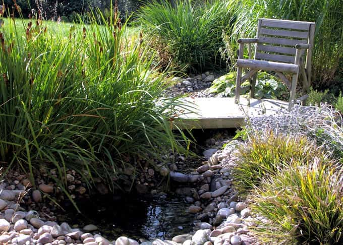 The stream emerges from beneath the decking bridge and spills into the small pebble pool
