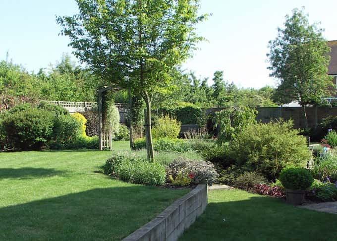 A sleeper wall retains the upper garden area which is now level and ideal for children\'s play