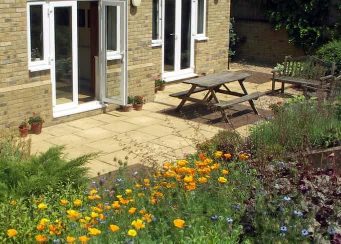 The patio nestles beneath a bank of shrubs and perennials