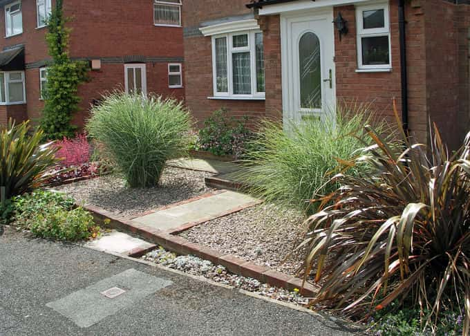 Two fine Miscanthus grasses flank the entrance path