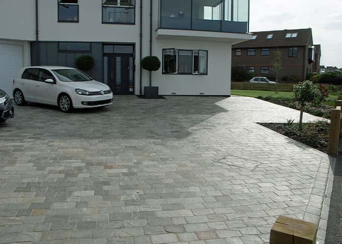 Beautiful natural stone block paviors elevate this driveway beyond the functional