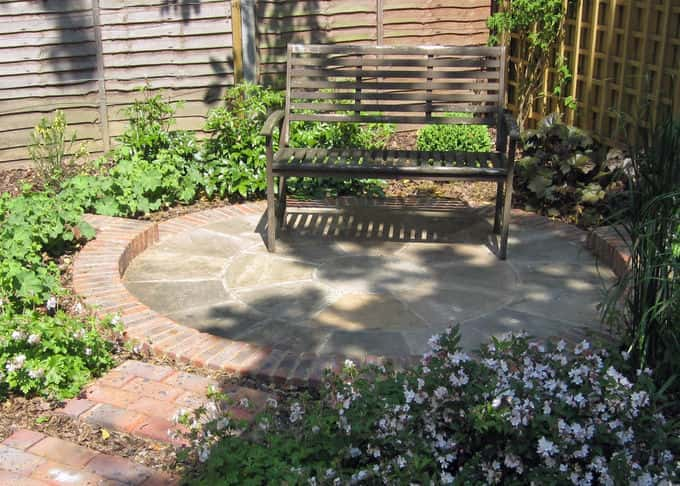 A charming sunken patio offers respite in dappled shade