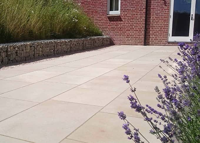 The clean lines of sawn York stone contrast with the industrial chic of ragstone gabion seats
