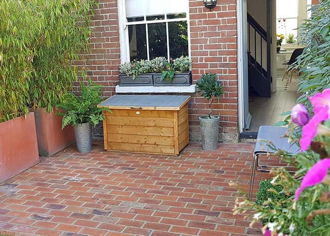 Traditional clay brick paving creates an intimate space in a small terrace garden