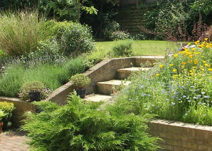 A wall and steps in yellow stock bricks makes a steep bank both manageable and attractive
