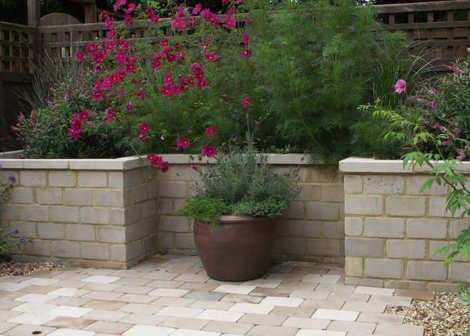 A raised bed in cool stone shows off vibrant planting