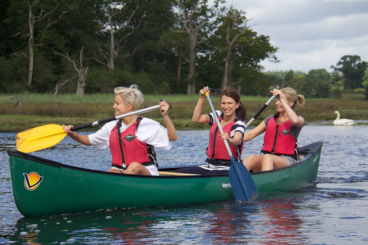 A group of ladies canoeing after looking for fun activities for adults in The New Forest.