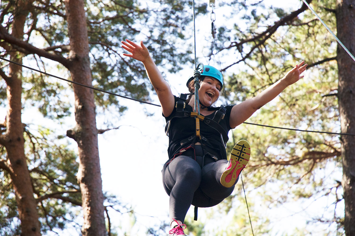 A woman taking part in high ropes after a back to business coaching workshop