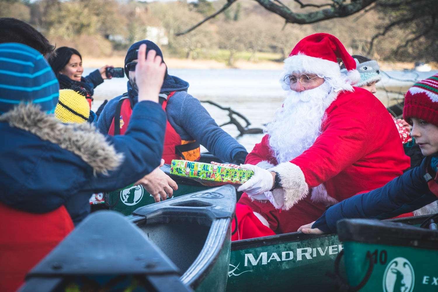 A group of children receiving gifts from Santa on the Beaulieu River.