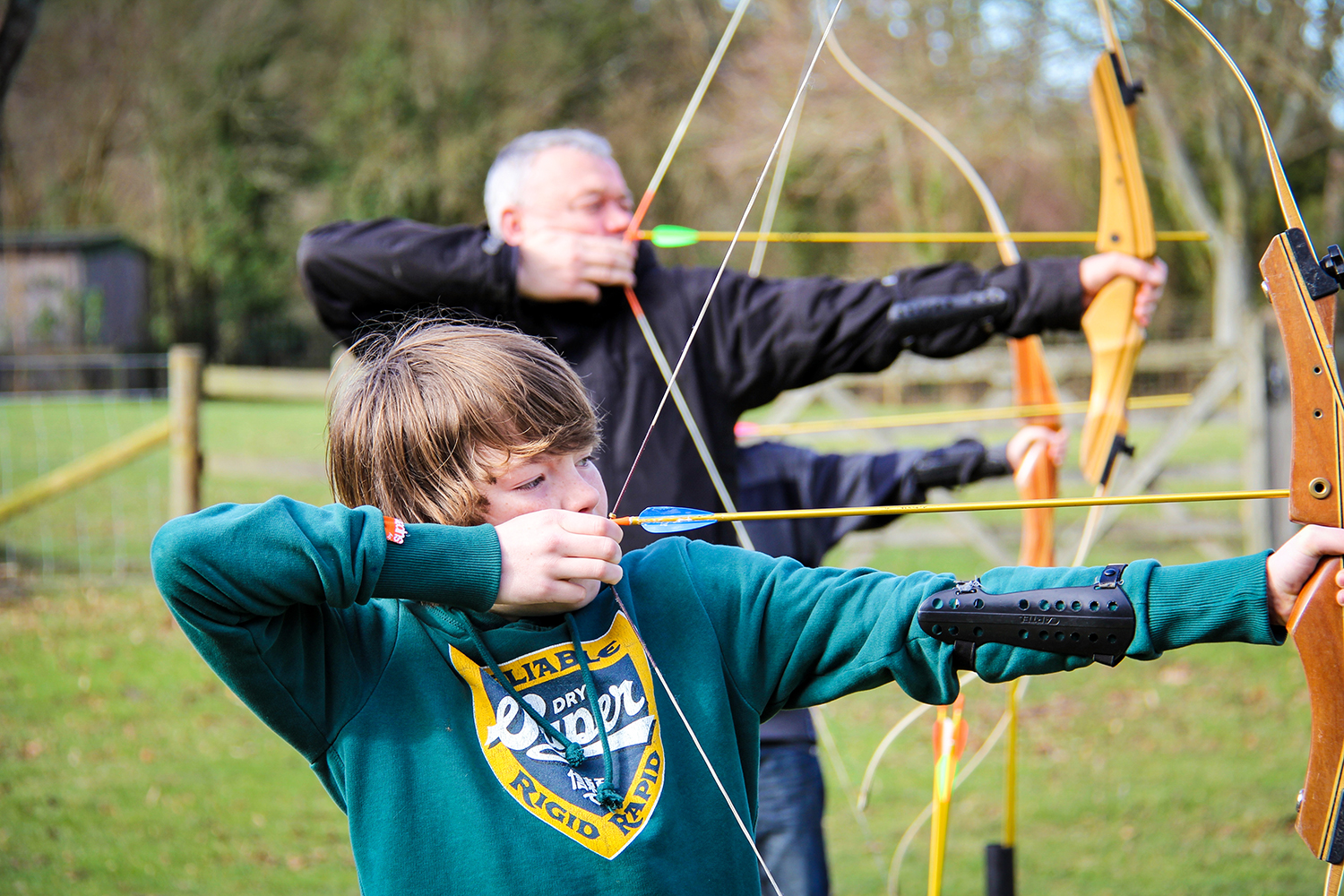 A father and son enjoying a winter archery session.