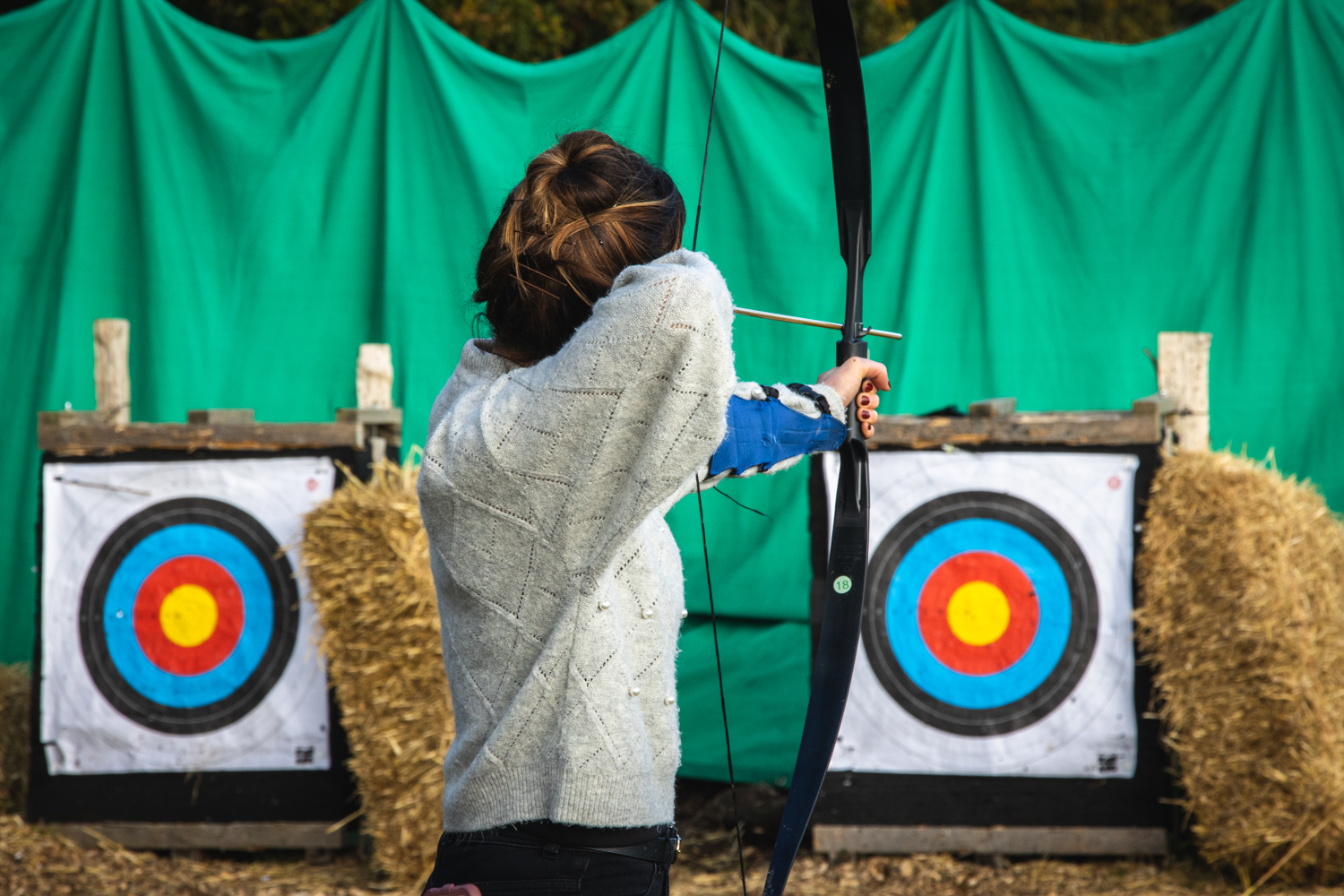 A Mother enjoying a winter archery session with her family.