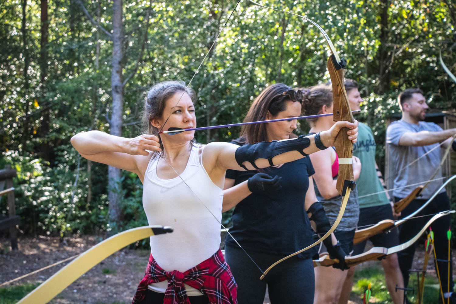 A group of colleagues taking part in archery during a back to business team building workshop