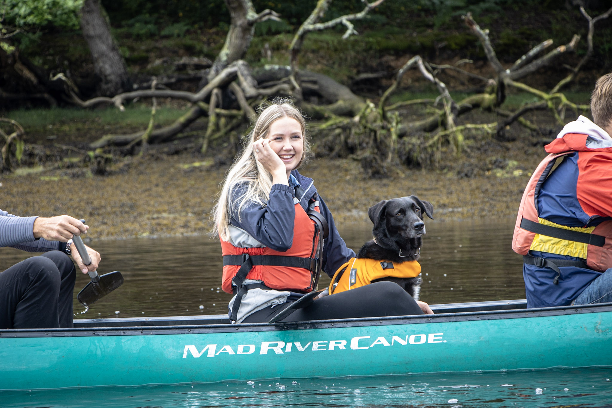Lady with dog in a canadian-style canoe.