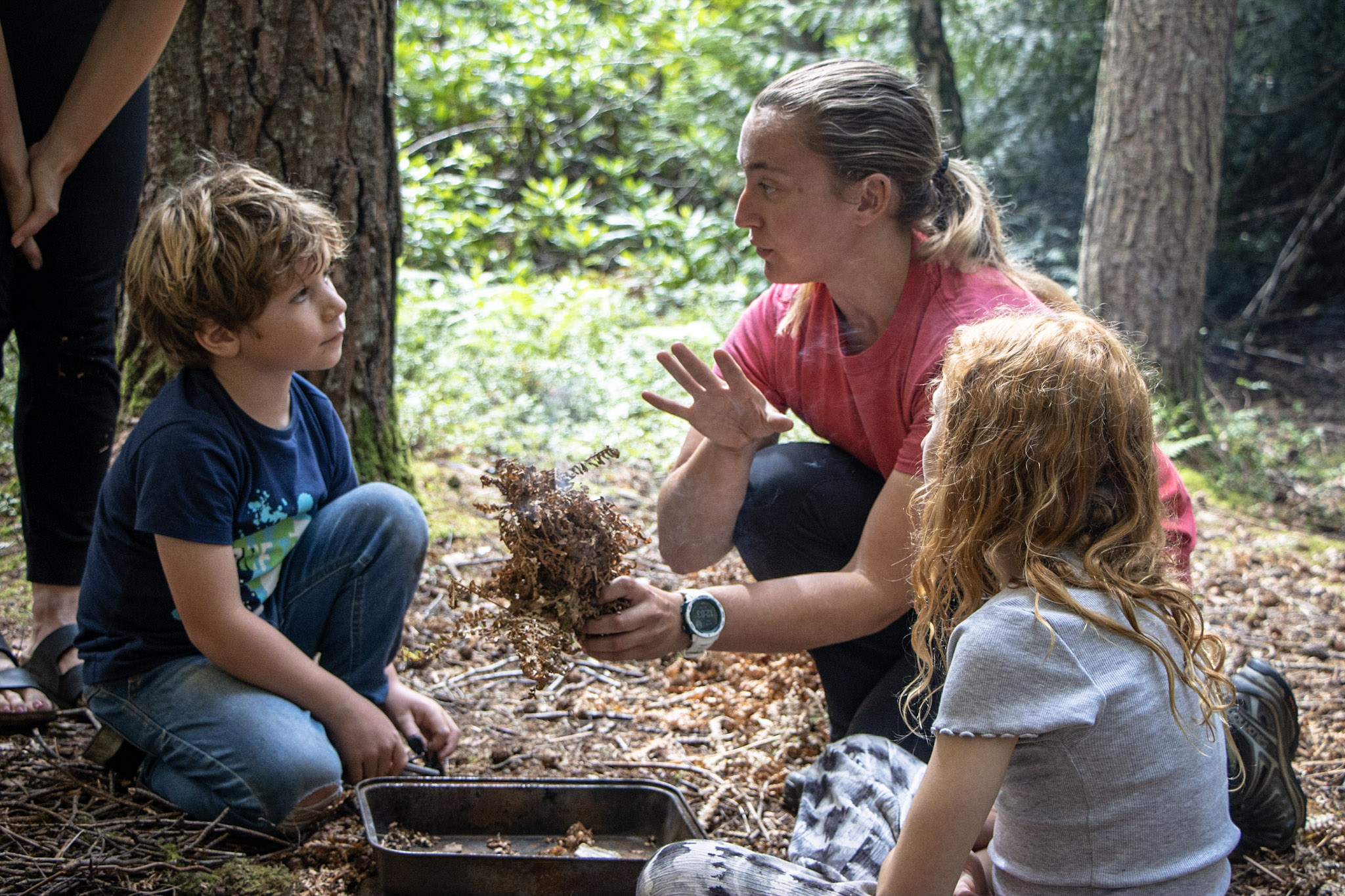 A family being taught how to make fire on a Woodland Adventure Day.